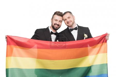 Photo for Smiling homosexual wedding couple holding lgbt flag isolated on white - Royalty Free Image