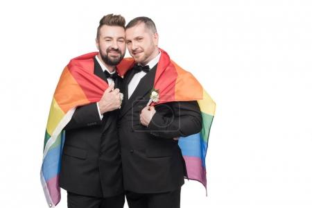 Photo for Young homosexual wedding couple embracing with lgbt flag isolated on white - Royalty Free Image