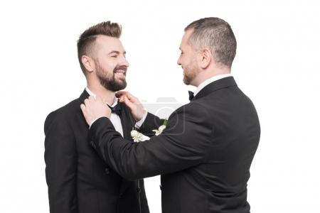 man fixing bow tie of groom