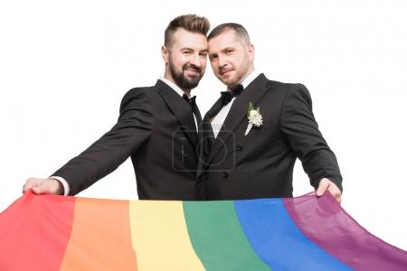 Photo for Homosexual wedding couple holding lgbt flag and looking at camera isolated on white - Royalty Free Image