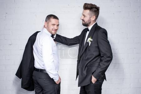 Photo for Smiling couple of grooms in tuxedos posing during wedding day - Royalty Free Image