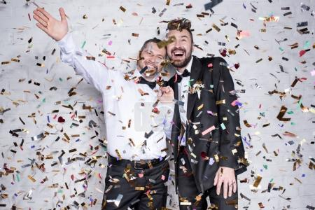 Photo for Happy homosexual couple in suits smiling and celebrating wedding with confetti - Royalty Free Image