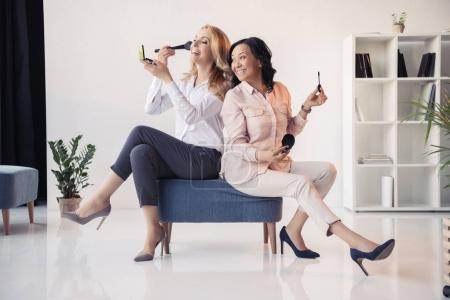 Photo for Two smiling middle aged businesswomen sitting together and applying makeup in office - Royalty Free Image