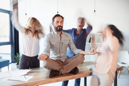Photo for Middle aged businessman sitting on table and meditating in lotus position while colleagues running around - Royalty Free Image