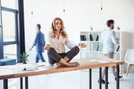 Businesswoman meditating in office