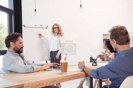 Photo pour Femme d'affaires souriante dans les lunettes pointant vers le tableau blanc vierge et regardant ses collègues - image libre de droit