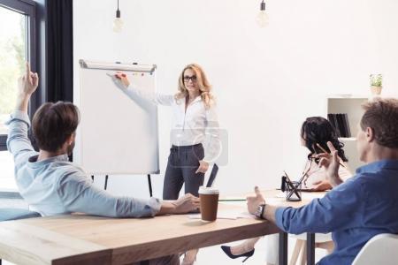 Photo pour Femme d'affaires blonde dans les lunettes pointant vers le tableau blanc vierge et regardant ses collègues - image libre de droit