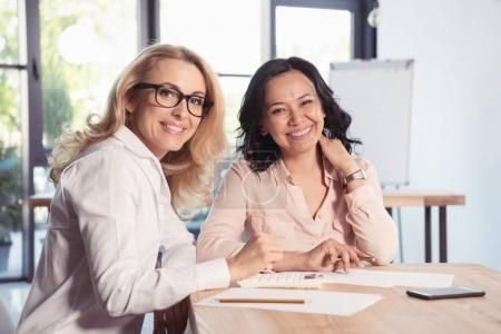 Photo for Beautiful middle aged businesswomen working together in office and smiling at camera - Royalty Free Image