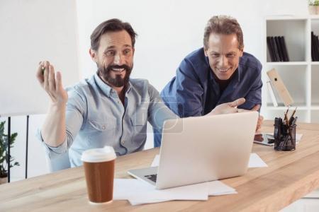 Hommes d'affaires, boire du café et à l'aide d'ordinateur portable