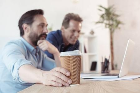 Businessmen drinking coffee and using laptop