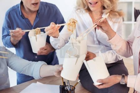 Photo pour Plan recadré de collègues d'affaires tenant des boîtes à nourriture et mangeant des aliments asiatiques avec des baguettes - image libre de droit
