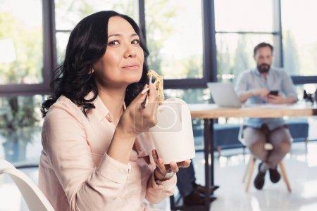 Mature asian businesswoman eating noodles