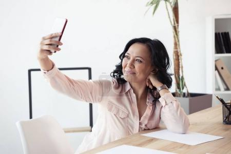 mature asian businesswoman taking selfie
