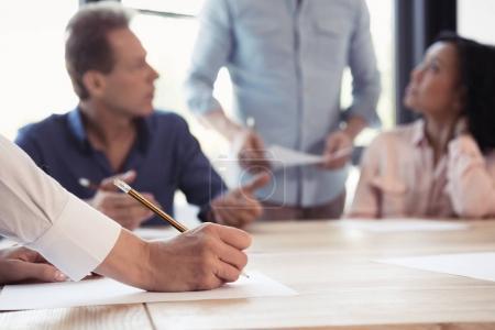 Photo pour Plan recadré de la femme prenant des notes lors d'une réunion d'affaires au bureau - image libre de droit