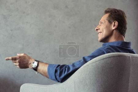 Photo pour Souriant homme d'âge moyen assis sur un fauteuil et pointant du doigt - image libre de droit