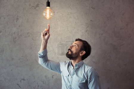 Photo for Middle aged man pointing with finger at illuminated light bulb - Royalty Free Image