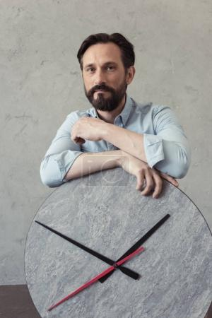 Pensive bearded man leaning on clock
