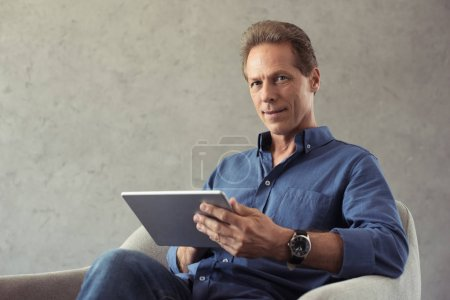 mature man using digital tablet