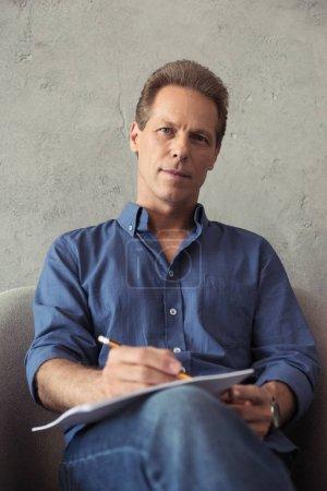 Photo pour Portrait de l'artiste mature, dessin au crayon, tout en étant assis sur le fauteuil à l'intérieur - image libre de droit