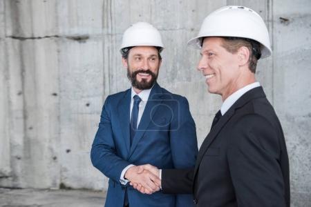 Photo pour Architectes professionnels matures dans des casques serrant la main et souriant - image libre de droit