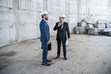Photo pour Deux architectes professionnels matures avec un plan de travail sur site de construction - image libre de droit