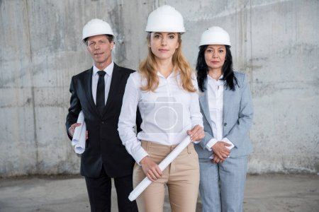 Photo for Professional team of architects in helmets holding blueprints and looking at camera - Royalty Free Image