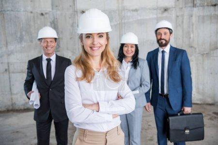 Foto de Equipo profesional de arquitectos en cascos juntos de pie y sonriendo a cámara - Imagen libre de derechos