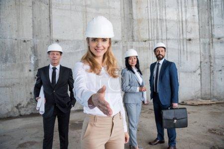 Photo pour Femme d'affaires blonde souriante au casque prête pour la poignée de main et collègues debout derrière - image libre de droit