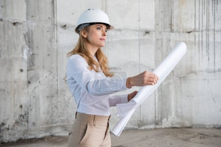 Photo for Beautiful blonde architect in helmet working with blueprint and looking away at construction site - Royalty Free Image