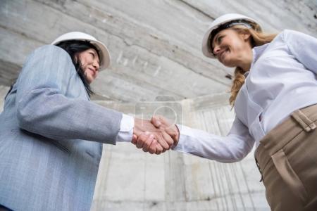 Photo pour Vue faible angle d'architectes professionnels casques se serrant la main et le sourire de l'autre - image libre de droit
