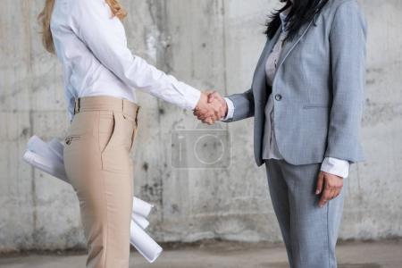 Photo pour Plan recadré de deux femmes d'affaires avec des plans serrant la main sur le chantier de construction - image libre de droit