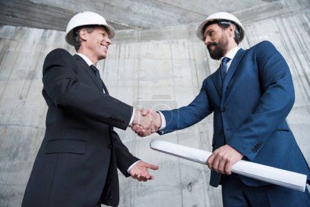 Foto de Vista de ángulo bajo de profesionales arquitectos en cascos de estrecharme la mano y sonriendo unos a otros - Imagen libre de derechos