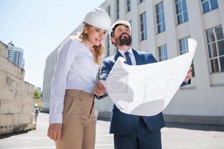 Foto de Profesionales de la arquitectura edad mediados en cascos holding blueprint y mirando en el edificio - Imagen libre de derechos