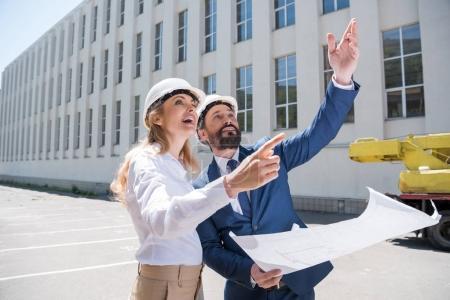 Photo pour Deux architectes souriants tenant blueprint et discuter du projet tout en travaillant - image libre de droit