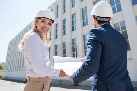 Photo pour Deux architectes professionnels en hardhats tenant un plan directeur tout en travaillant sur le chantier - image libre de droit
