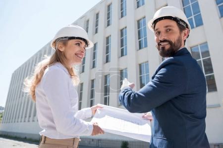 Photo pour Homme d'affaires souriant et femme d'affaires dans des casques tenant le plan directeur et pointant vers le bâtiment - image libre de droit