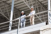 architects in formal wear standing at construction