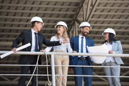 Photo for Middle aged architects in suits talking while standing at construction site - Royalty Free Image