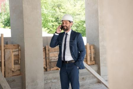 Smiling contractor talking on smartphone at construction