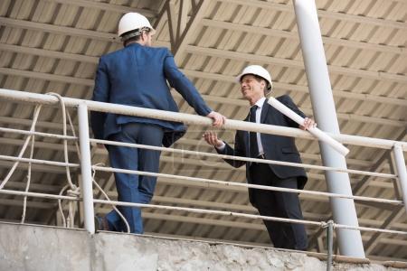Photo pour Entrepreneurs matures dans l'usure formelle parler sur le chantier de construction - image libre de droit