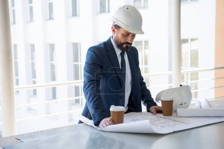 middle aged architect looking at blueprints