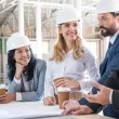 Multiethnic architects in suits working with blueprints