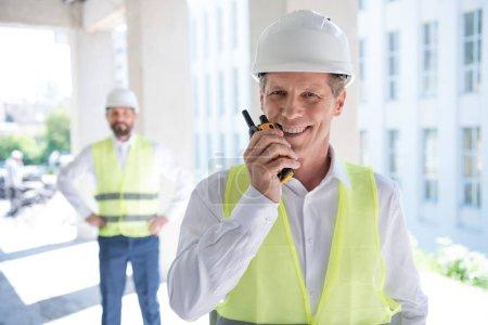 Mature constructor talking on radio set