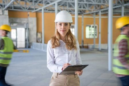 Photo for Mature contractor in helmet making notes at clipboard and looking at camera - Royalty Free Image