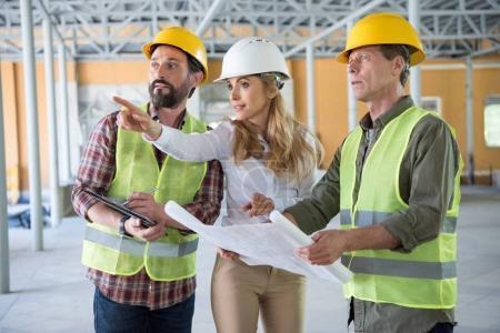 Photo pour Constructeurs matures et entrepreneur parler pendant les travaux sur le chantier de construction - image libre de droit