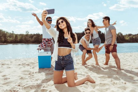Photo for Group of cheerful friends taking selfie together on smartphone on beach - Royalty Free Image