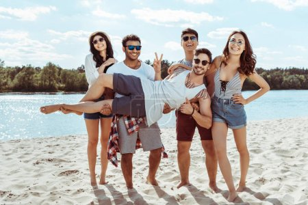 Photo for Cheerful friends holding man in hands and looking at camera on beach - Royalty Free Image