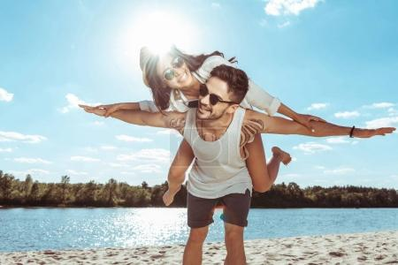 couple piggybacking on beach