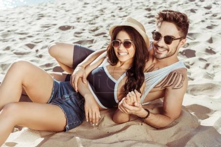 Photo for Happy young couple relaxing on beach together on summer day - Royalty Free Image