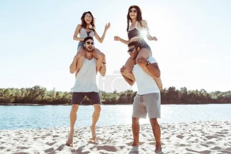 Photo for Happy friends piggybacking and enjoying summertime while spending time on beach - Royalty Free Image